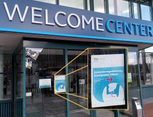 """Moderner Eingangsbereich mit großen Buchstaben """"WELCOME CENTER"""", an der Glaswand ein Schild, grafisch im Bild vergrößert: Logo der Stadt Kiel, darunter: """"Zuwanderungsabteilung (Immigration Office)"""" und ein Pfeil nach rechts."""